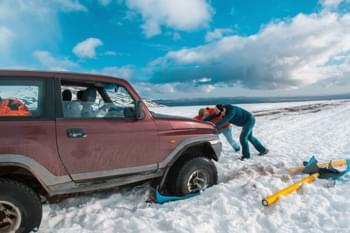 Männer schieben Auto aus Schnee
