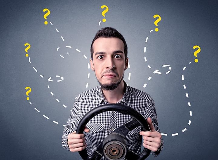 Mann mit Lenkrad und Fragezeichen